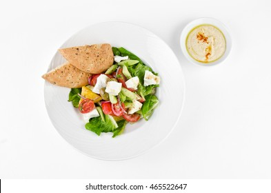 Greek salad with feta cheese, Ligurian olives and tortilla pea and hummus on a plate on a white background, top view