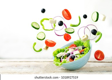 Greek Salad with flying ingredients to prepare it on a white background