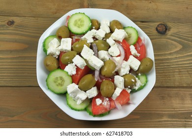 Greek salad from fresh organic vegetables: chopped red onion, tomatoes cut on wedges, sliced seedless cucumber; and stuffed green colossal olives, cubes goat Feta Cheese in white dish on wooden table