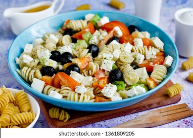 Greek salad with fresh vegetables, feta cheese, pasta and black olives