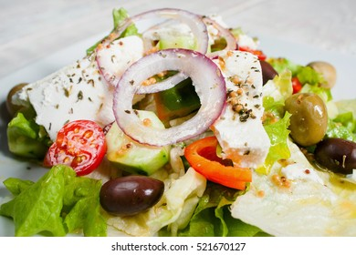 Greek salad with fresh vegetables and feta. Close-up of appetizing side dish with olives and cheese. Mediterranean cuisine, restaurant food, menu concept