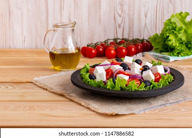 Greek salad with fresh vegetables on wooden background, feta cheese and black olives. Love for healthy raw food concept.