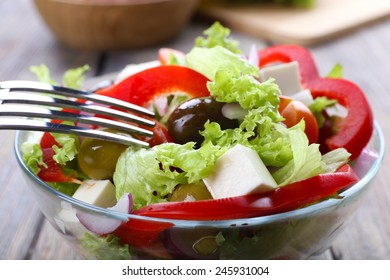 Greek salad in glass dish with fork on wooden table background