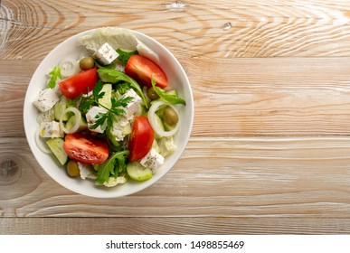 Greek salad or horiatiki with large pieces of tomatoes, cucumbers, feta cheese and olives in white bowl top view, copyspace. Village salad with diced mozzarella, arugula, parsley, spices and oil - Shutterstock ID 1498855469