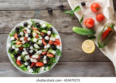 Greek salad and Ingredients on old boards. Flat lay