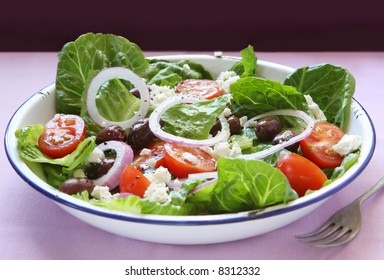 Greek salad in old enamel bowl.  Delicious romaine lettuce, cherry tomatoes, crumbled feta cheese, cucumber and black kalamata olives.