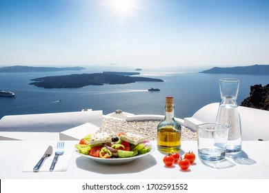 A Greek salad with olive oil and tomatoes in front of the a breathtaking view to the blue, Aegean sea as a concept of Greek food in summer time