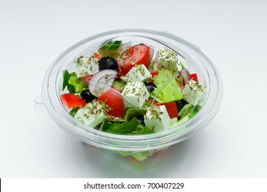 Greek salad in plastic container isolated on a white background.  Salad for take away or food delivery