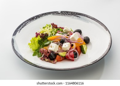 Greek salad in a plate isolated on a white background.