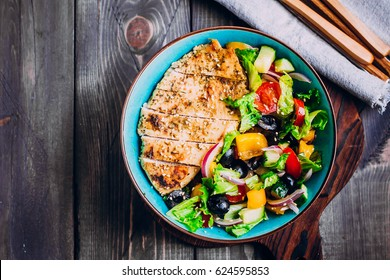 Greek salad and roasted chicken in plate  on wooden table background. Top view with copy space