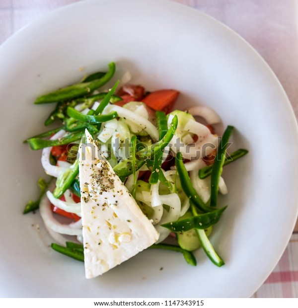 Greek salad with sheep Feta Cheese on white plate on a table in a Mediterranean Restaurant