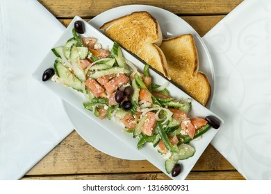 Greek Salad with Toast Bread on Wooden Table
