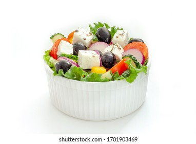 Greek salad with tomato and fresh vegetables in white bowl on white background.