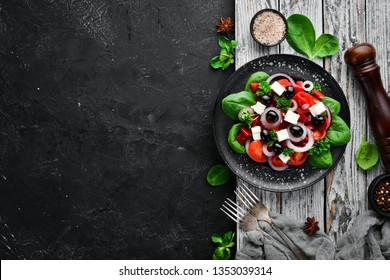 Greek salad with tomatoes, paprika, onions and feta cheese. In a black plate on a wooden background Top view. Free space for your text. Flat lay