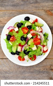 Greek salad (top view) on a wooden table