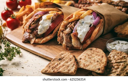 Greek souvlaki, gyros wrapped in pita breads on a wooden background