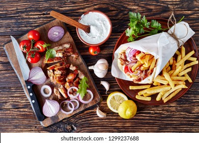 greek souvlaki - pita wrap with grilled shaved gyros meat, vegetables, french fries and yogurt garlic sauce, ingredients on a cutting board on a rustic table, view from above, flat lay