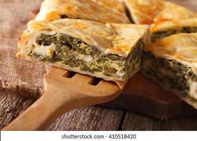 Greek spanakopita piece of pie on the table macro. horizontal