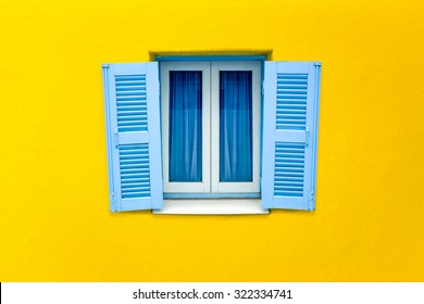 Greek style window on yellow concrete wall color