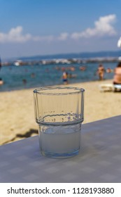 Greek tavern alcoholic drink. Ouzo on the rocks served on a glass in blurred beach background.