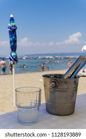 Greek tavern alcoholic drink. Ouzo on the rocks with ice cubes container served on a glass in blurred beach background.