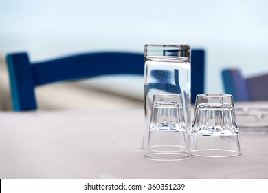 Greek tavern with blue wooden chairs by the aegean sea coast, Greece