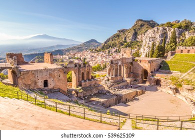 The Greek Theater stage with the vulcan Etna, mountains and Castelmola in the background. Taormina, Sicily, Italy