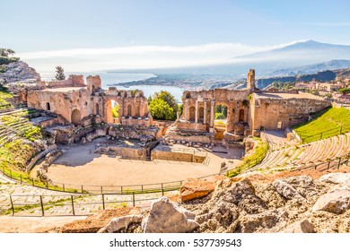 The Greek Theater of Taormina burning in the sunshine with Giardini-Naxos and the Etna in the background, Taormina, Sicily, Italy