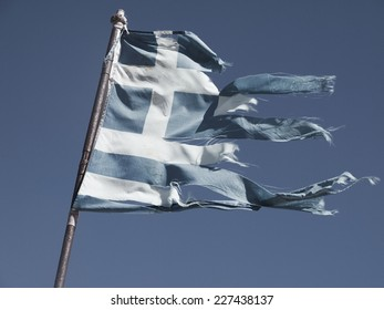 Greek torn flag fluttering in the wind, posted signs on a rusty pole