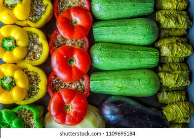 Greek traditional food Gemista. Stuffed  peppers, tomatoes, zucchini, eggplant, potato and vine leaves with rice, vegetables and herbs. Top view