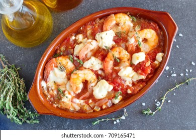 Greek traditional food. Oven backed prawns with feta, tomato, paprika, thyme in a traditional ceramic form on a abstract background. Healthy eating concept. Mediterranean lifestyle.