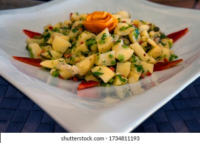 Greek traditional Potato Salad served in a square white dish, decorated with sliced red peppers, parcel, capers and other herbs