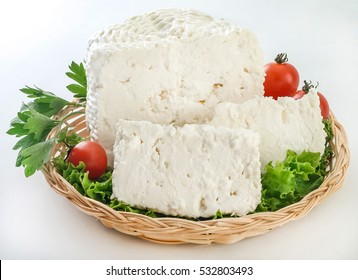 """Greek traditional white cheese called """"kalathaki"""" meaning small basket.The cheese is made from goat and sheep's milk.White background"""