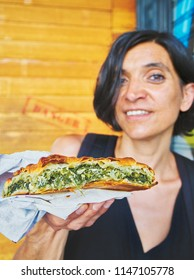 Greek woman eating a traditional Spanakotiropita, Spinach and Feta cheese pie, typical greek street food.