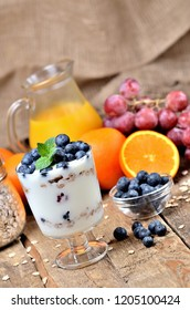 Greek yoghurt with oatmeal, fresh blueberries and mint leaves and orange and grapes in background vertical photo