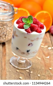 Greek yoghurt with oatmeal and fresh raspberries in a glass and mint leaves, full glass of oatmeals and oranges in background