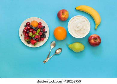 Greek yogurt around orange, banana, pear, peach, apple, plate of strawberries, raspberries, blueberries and 2 spoons on light blue background.  Yogurt and fruits, berries as an ingredients. Top view.