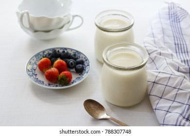 Greek yogurt with fresh blueberry and strawberry in a glass jars on wooden background.