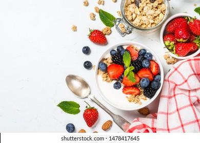 Greek yogurt granola with fresh berries on white table, top view, copy space. Healthy food, snack or breakfast.