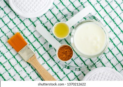 Greek yogurt (sour cream or kefir) facial mask with turmeric powder and olive oil. Ingredients of diy face and hair masks and moisturizers. Homemade beauty treatments recipe. Top view.
