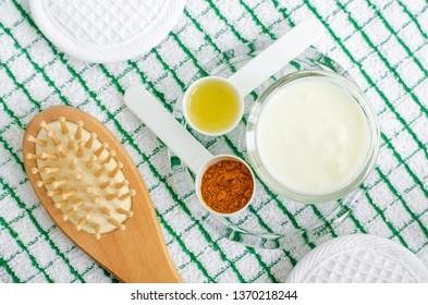 Greek yogurt (sour cream or kefir) facial mask with turmeric powder and olive oil. Wooden hair brush. Ingredients of diy face, hair masks and moisturizers. Homemade beauty treatments recipe. Top view.