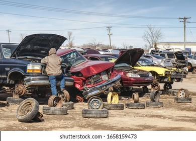 Greeley, Colorado, USA - February 27, 2020. Shade-tree mechanics search through wrecked vehicles for parts to repair their own vehicles.  Salvage yards  are recyclers.