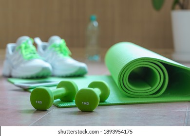 Green 1 kg dumbbells and exercise mat on the floor, blurred background with sneakers and bottle of water. Equipment for physical workout at home. Active healthy lifestyle concept.