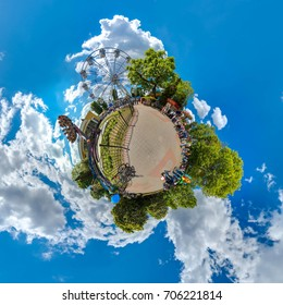 Green 360 little planet with trees, white clouds and soft blue sky. Tiny planet of amusement park. 360 viewing angel. Planet Earth.