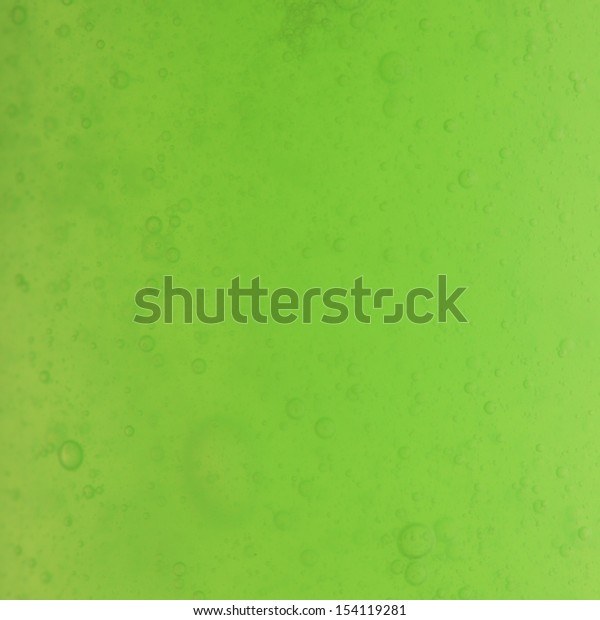 Green abstract blurred liquid background with soap bubbles. Square format
