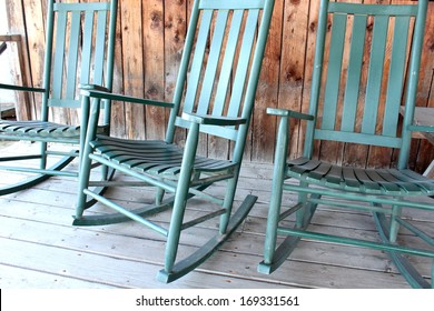 Green Adirondack rocking chairs on old wood porch welcome visitors to sit and relax for awhile.
