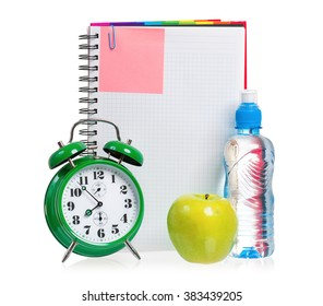 Green alarm clock, apple and bottle of water with blank notebook as concept of diet - isolated on white