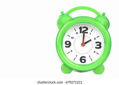 green alarm clock with the hands at 2 am or pm isolated on a white background.