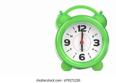 green alarm clock with the hands at 6 am or pm isolated on a white background.