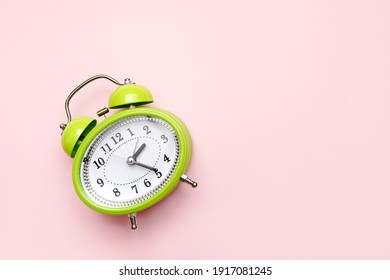 green alarm clock on pink background with copy space